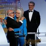 Bei der Eröffnungsgala der Filmfestspiele begrüßt Jurypräsidentin Jane Campion den britischen Musiker Michael Nyman. Zeremonienmeister Lambert Wilson betrachtet das wohlwollend.
