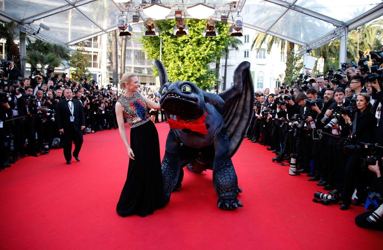 """Cate Blanchett posiert auf dem roten Teppich mit einer Figur aus dem Film """"How to Train Your Dragon 2""""."""