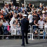 Ein paar Fans bitten einen Polizisten ein Foto von ihnen zu machen.