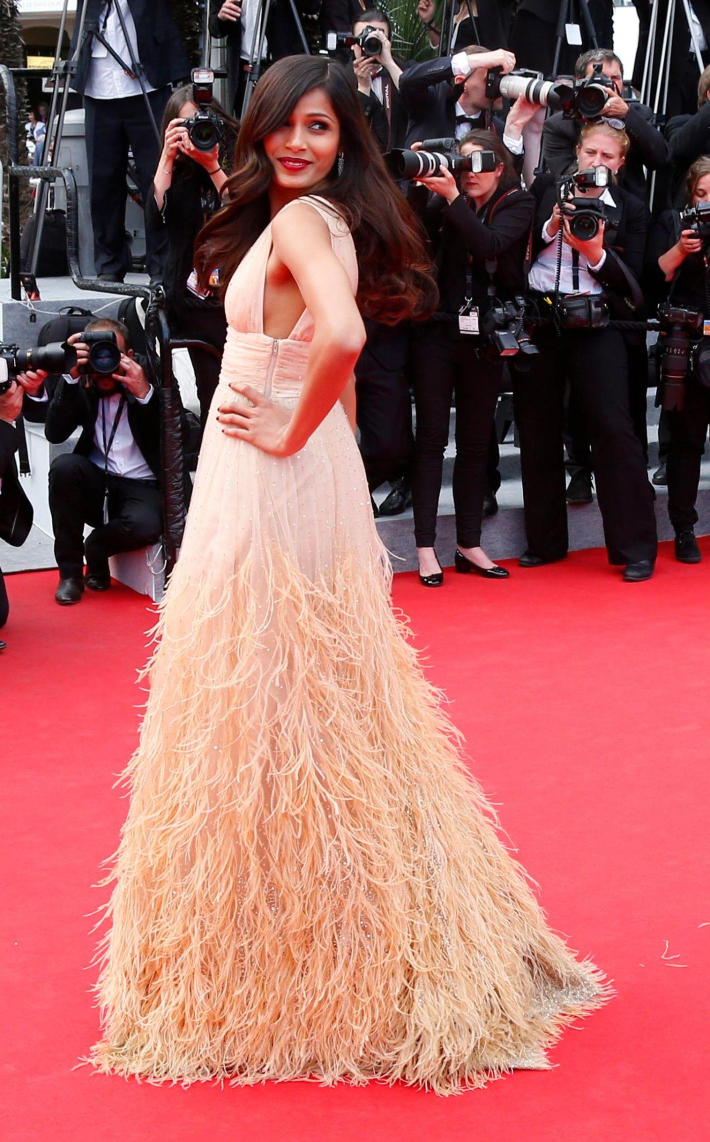 Freida Pinto trägt ein mit Federn besetztes Kleid im Nude-Look.