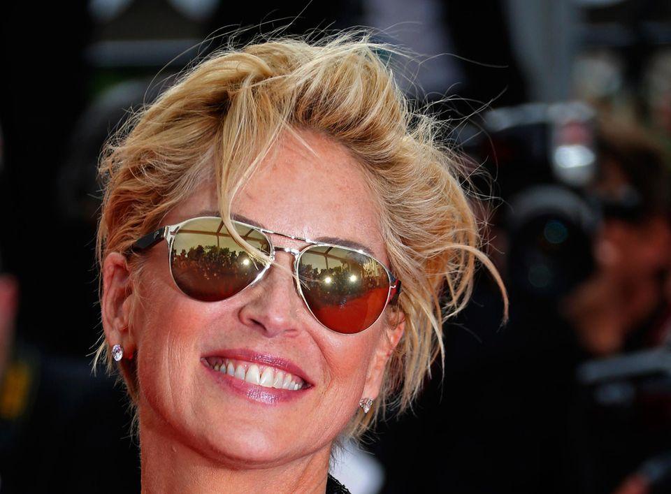In Sharon Stones Sonnenbrille spiegeln sich die Blitzlichter der Reporter.