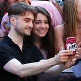 """Daniel Radcliffe übernimmt das Fotografieren mit dem """"Pink""""-Handy des weiblichen Fans in der ersten Reihe."""