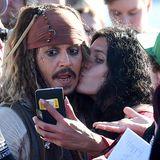 """Dieser Fan schnappt sich für ein Selfie Johnny Depp und drückt """"Captain Jack Sparrow"""" sogar ein Küsschen auf."""