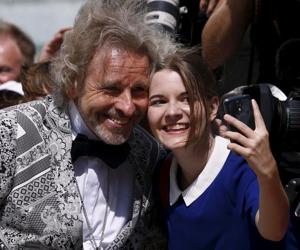 Dieser junge Fan schnappt sich Thomas Gottschalk für ein Selfie. Der Star ist auf dem Weg ins Bayreuther Opernhaus.
