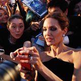 """Angelina Jolie macht mit dem Handy eines Fans ein Selfie auf dem roten Teppich der Tokio-Premiere von """"Maleficent""""."""