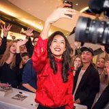 Um gleich eine ganze Gruppe von Fans mit auf das Foto zu bekommen, nimmt Rebecca Mir das Smartphone selbst in die Hand. Einen Selfie-Stick benötigt die hübsche Moderatorin, die in ihrer roten Bluse besonders in den Fokus der Aufnahme rückt, dafür nicht.