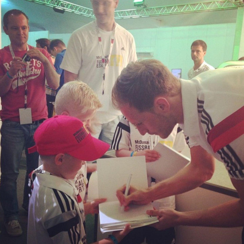 Benedikt Höwedes gibt seinen jüngsten Fans Autogramme.