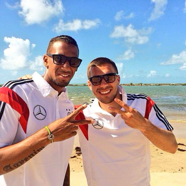 Jérôme Boateng und Lukas Podolski lassen sich am Strand die Sonne auf den Kopf scheinen.