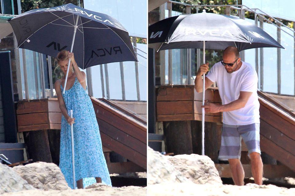 Schön zu sehen, dass auch die Stars mal Alltags-Probleme haben: Rosie Huntigton-Whiteley und Jason Statham versuchen am Strand von Malibu einen Sonnenschirm aufzubauen.