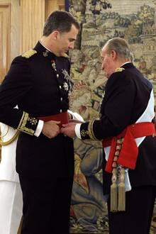 Juan Carlos legt Felipe die Schärpe um.