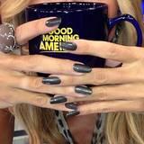 """Den großen Kaffeepott umschließt Heidi Klum dekorativ mit ihren Raubtierkrallen und verbreitet gute Laune in der Sendung """"Good Morning America!""""."""