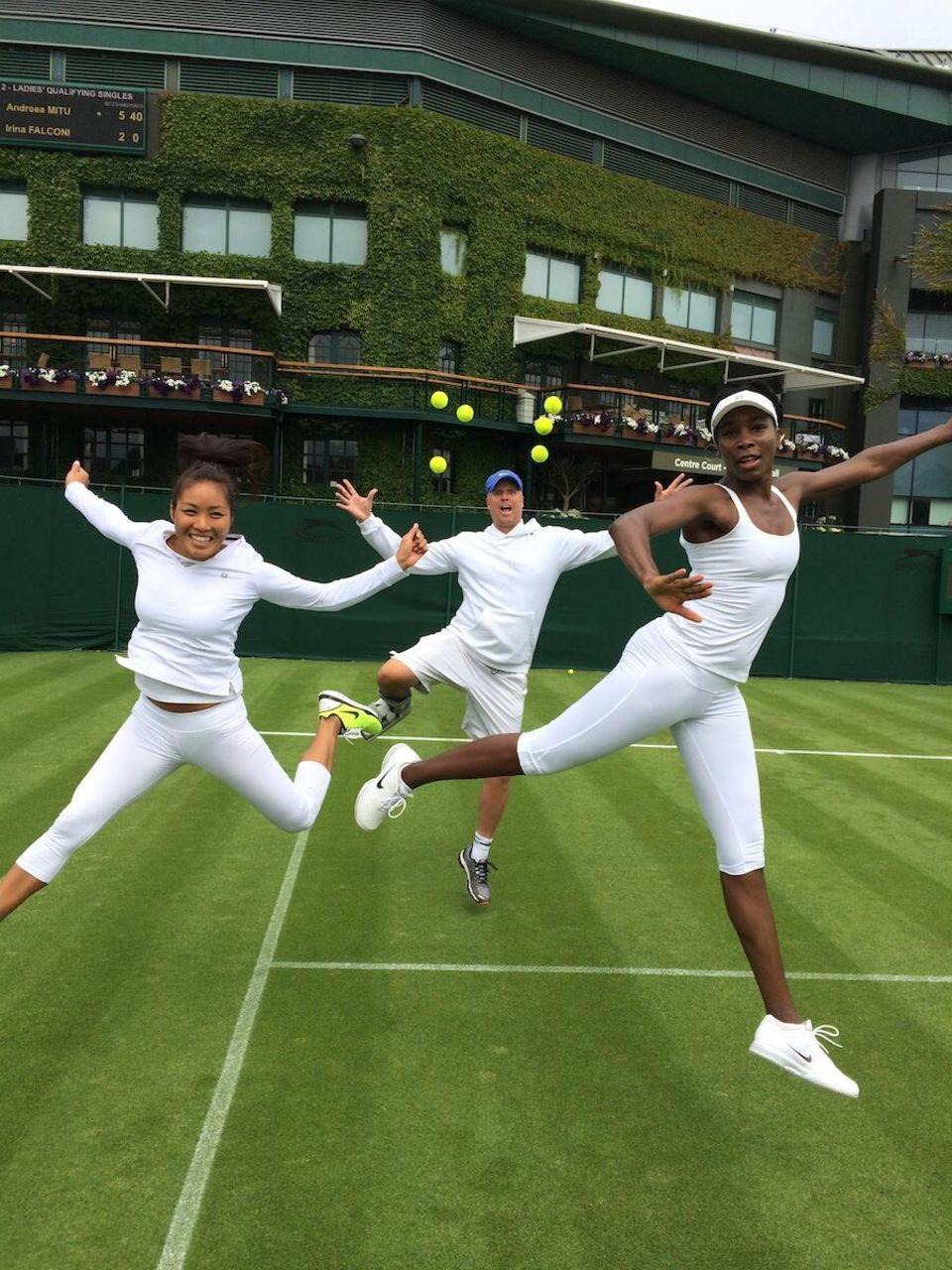 Venus Williams springt mit ihrem Team auf dem heiligen Rasen herum.