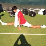 Novak Djokovic dehnt sich ausgiebig nach dem Training. Boris Becker hält das auf Kamera fest.