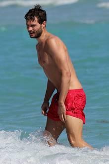 """""""Shades of Grey""""-Beau Jamie Dornan begeistert am Strand mit seinem definierten Körper. Da wünscht man sich doch eigentlich, dass die rote Badehose noch ein wenig weiter hochrutscht, oder?"""