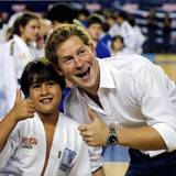 """Daumen hoch für das Erinnerungsfoto: Prinz Harry posiert mit einem jungen Athleten im """"Minas Tênis Clube""""."""