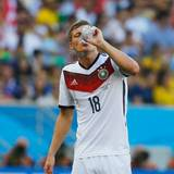 Toni Kroos trinkt noch, als schon die nächste Wasserflasche geflogen kommt.