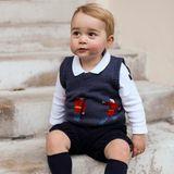 Prinz George trägt auf seinen Weihnachtsfotos eine kurze, schwarze Hose und dazu einen blauen Pullunder. Darauf zu erkennen sind, wie es sich für einen englichen Prinzen gehört, Gardisten mit Bärenfellmützen.