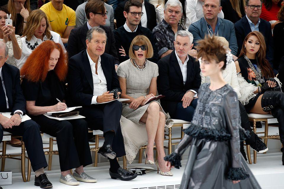 Vogue-Chefin Anna Wintour scheint begeistert zu sein von Karl Lagerfelds neuesten Kreationen. Mit ihr in der Front Row sitzen auch Star-Fotograf Mario Testino (l.) und Regisseur Baz Luhrmann (r.).
