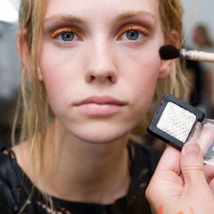 Der Teint sonnengeküsst, die Augen mit leuchtendem Orange als Kontrast: Bei Lala Berlin sind die Stylisten der Kosmetikmarke Catrice am Werk.