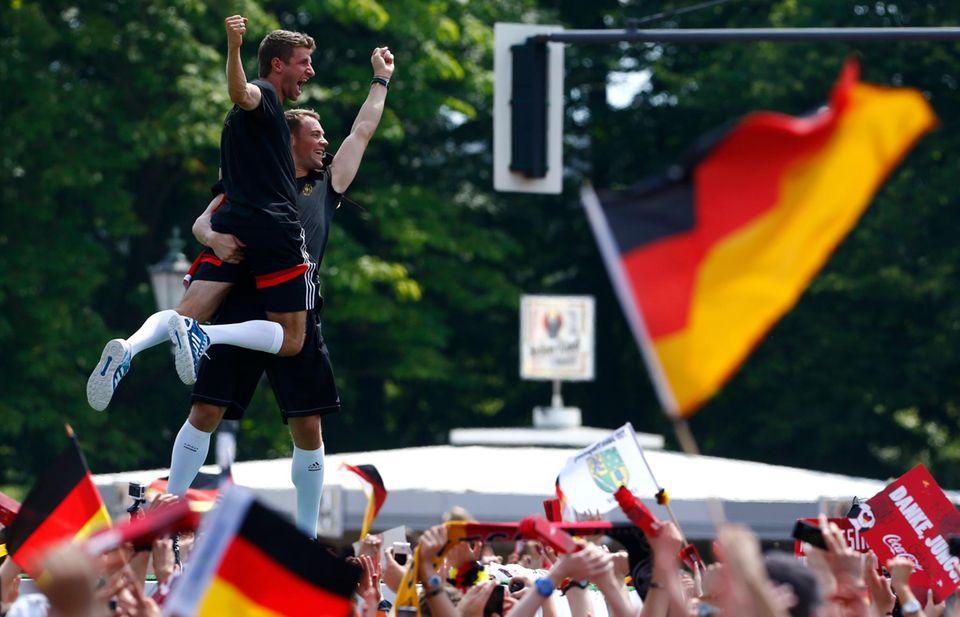 Manuel Neuer und Thomas Müller scheinen vor lauter Jubel auf der Fanmeile fast zu schweben.