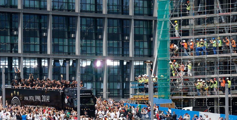 Hunderttausende säumen den Weg vom Flughafen zur Fanmeile am Brandenburger Tor und jubeln den neuen Fußballweltmeistern zu. Selbst die Bauearbeiter lassen für Neuer, Schweinsteiger, Özil und Co. alles stehen und liegen. Wegen der Fanmassen musste der WM-Truck immer wieder stoppen.
