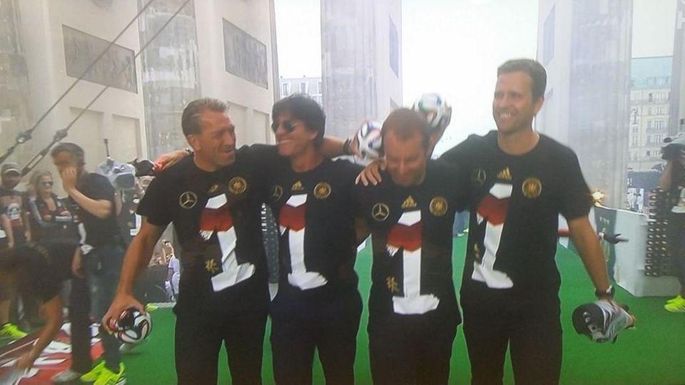 Um 13 Uhr sind die Weltmeister am Brandenburger Tor angekommen. Jogi Löw und sein Trainerteam haben die Ehre als Erste auf der Bühne aufzutreten. Alle tragen das Weltmeister-Trikot mit der Nr. 1.