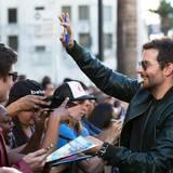 Bradley Cooper gibt seinen Fans vor der Premierenfeier Auotgramme.