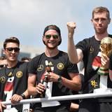 Jubelnd stehen Mesut Özil, Benedikt Höwedes und Per Mertesacker im offenen Mannschaftsbus.