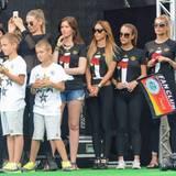 Die Frauen und Kinder der Spieler stehen hinter der Bühne und beobachten das Geschehen.