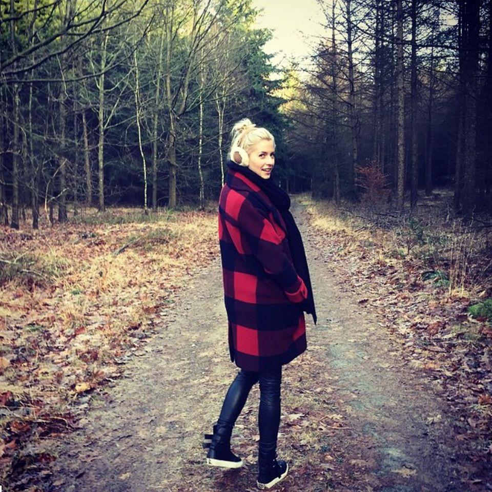 Lena steht im Walde und sieht toll aus! Der Mantel mit den großen Karos ist von Tommy Hilfiger. Dazu trägt sie Sneakers und gegen die Kälte, süße Ohrenschützer.