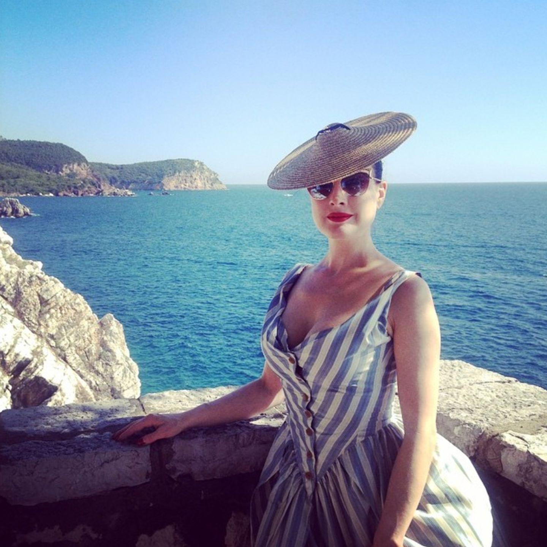 Die sonst so burlesque Dita von Teese wirkt auf ihren Instagram-Urlaubsgrüßen wie auf einer Postkarte aus den Fifties: Tellerstrohhut mit gestreiftem und geknöpftem Sommerkleid passen toll zum Strand-Look.