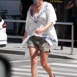 """""""Game of Thrones""""-Star Lena Headey trägt im Sommer einen witzigen Mix aus Fransenshorts, Bikinioberteil und weißer Tunika, die sie vorne in den Bund des Shorts gesteckt hat, damit ein wenig Körperkontur zu erkennen ist."""