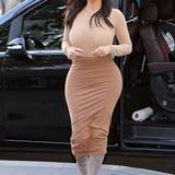 """Zu ihre hautengen Kleider stylt Kim am liebsten hohe Schuhe. Bei diesem Outfit setzt der """"Keeping up with the Kardashians""""-Star auf erdige Farbtöne und stylt zum langärmligen Shirt, wandenlangen Rock Wildlederstiefel."""