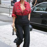 Mit einer karierten Bluse im Holzfäller-Stil von Givenchy und einer Bundfaltenhose mit Schlag schafft Kim Kardashian den Spagat zwischen lässig und edel. Ihre extravagante Fransen-Handtasche von Alexander McQueen im Wert von ca. 1500 € fungiert dabei als ist echter Hingucker.