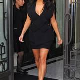 Ihrer Vorliebe für schwarze, edle Kleidung geht Kim Kardashian auch mit diesem raffiniert geschnittenen Kleid von Awake nach, welches sie zu Cut-Out-Sandalen aus dem Hause Hermés kombiniert.