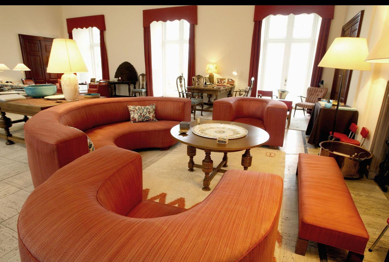 Um den Kamin herum sind Sofas und Sessel platziert. Bei den Möbeln mischen sich aber alte und neue harmonisch miteinander.