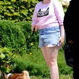 Lena Dunham liebt es lässig in Shorts und süßem Katzen-Sweatshirt. Die Kappe ihrer Sneakers hat sie gemütlich runtergetreten.