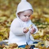 Zipfelmützchen und Strickcardigan sind für Estelle genau das Richtige zum Spielen im Herbstlaub.