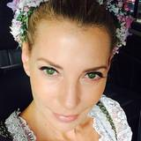 Um ihre streng nach hinten gestylte Frisur aufzulockern, hat sich Giulia Siegel für einen farbenfrohen Blumenkranz entschieden, den sie als Haarreif trägt.