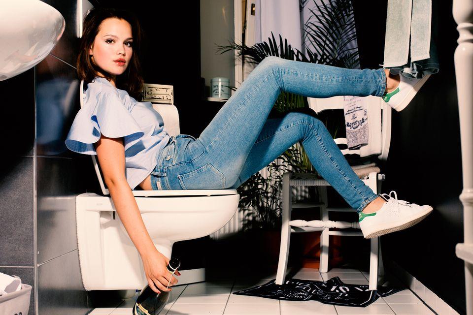 """Emilia Schüle Eine hellere Waschung, dazu eine Bluse aus einem klassischen Herrenstoff und Retro-Sneakers – fertig ist der burschikose Stil. (Jeans und Bluse von H&M, Schuhe """"Stan Smith"""" von Adidas Originals)"""