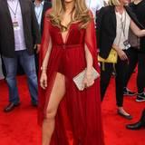 """Mai 2014:  Mit tiefblickenden Ausschnitten und viel Beinfreiheit steht Jennifer Lopez am allerliebsten auf dem roten Teppich. Zu den """"Billboard Music Awards 2014"""" trägt sie eine rote Robe von Donna Karan und kombiniert dazu goldene Sandaletten von Jimmy Choo."""