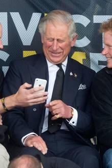 Was da wohl auf dem Handy zu sehen ist? William, Charles und Harry amüsieren sich jedenfalls prächtig.