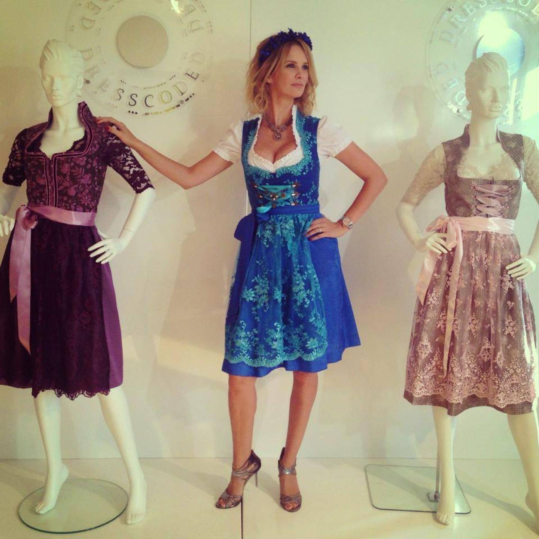 Monica Ivancan posiert beim Dirndl-Shopping mit zwei Schaufensterpuppen.