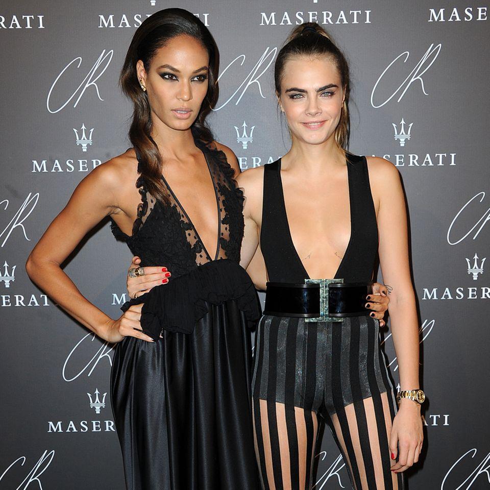 """Ganz in Schwarz und ziemlich freizügig: Die Topmodels Joan Smalls und Cara Delevingne halten sich genau an den vermeintlichen Dresscode des """"CR Fashion Book""""-Launchs."""