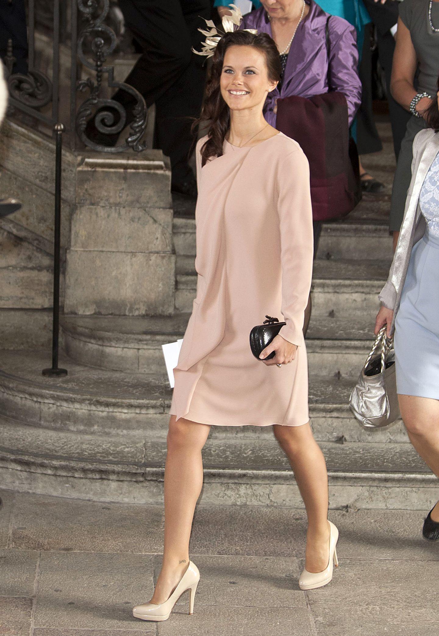 Die Taufe der kleinen Prinzessin Estelle im Mai 2012 war eines der ersten offiziellen Events, das Sofia Hellqvist absolviert hat. Im mattrosa Chiffon-Dress mit schicken Fascinator-Hütchen und nudefarbenen Pumps hat sie das modisch hervorragend gemeistert.