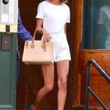 Mit gebräunten Mega-Beinen wie bei Taylor Swift sehen weiße Playsuits (dieser ist von Rachel Zoe) gleich noch viel besser aus. Passend dazu kombiniert die Pop-Sängerin Statement-Pumps in blauem Wildleder von Manolo Blahnik und eine elegante, beige Ledertasche von Michael Kors.