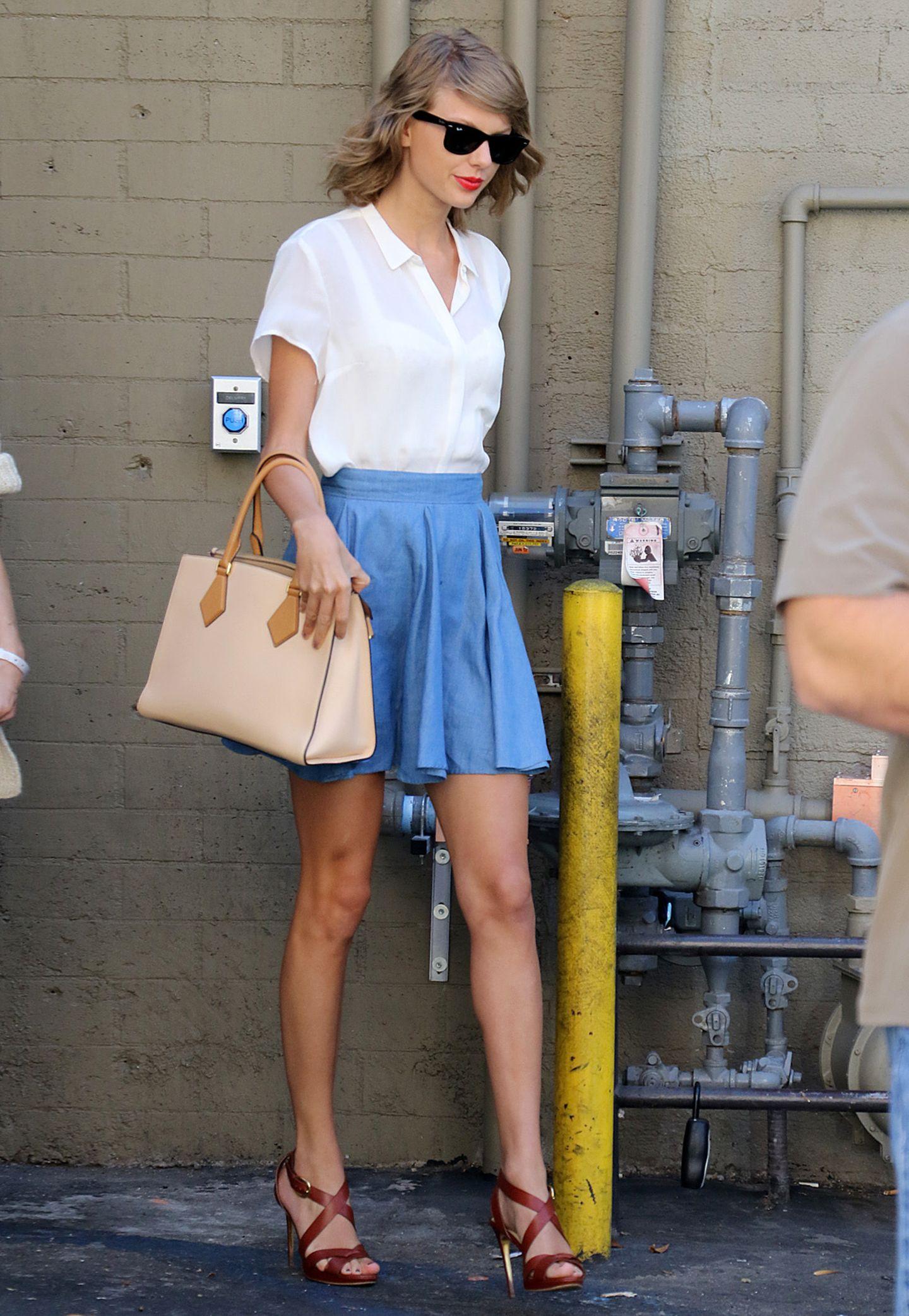 Mit diesem Outfit überstrahlt Taylor Swift ganz lässig die unansehnlichen Rohre im Hintergrund. Zu weißer Bluse und blauem Skater-Rock trägt sie eine elegante Henkeltasche in hellem Beige und braune Stilettos.