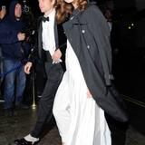 Eine gut gelaunte Keira Knightley bedeckt ihr weißes Kleid mit einem schwarzen Burberry-Trenchcoat.