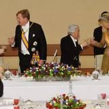 Gastgeber und Gäste prosten sich an der langen, festlich gedeckten Tafel zu.