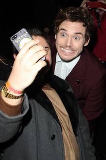 Sam Claflin photobombt einen Fan, der ein Selfie macht.
